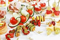 Närbildsiktsuppsättning av canapes med grönsaker, salami, skaldjur, M Fotografering för Bildbyråer