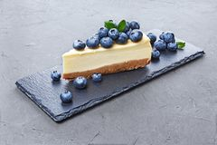 Närbildskivan av läcker hemlagad ostkaka med nya blåbär på svart kritiserar brädet royaltyfri bild
