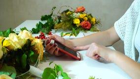 Närbildskott av blom- märkes- händer för flicka` s som använder mobiltelefonen för överensstämmelse på tabellen med nya blommor i stock video