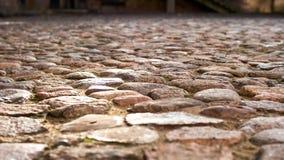 Närbildskott av den gamla fyrkanten som stenläggas med stora stenar för bakgrund Royaltyfria Bilder