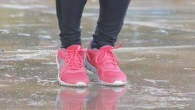 Närbildskott av den kvinnliga foten i rosa gymnastikskor Kvinnabanhoppning på ett rep i regnet arkivfilmer