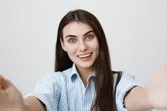 Närbildskott av den snälla och lyckliga kvinnan som ler ar-kameran, och innehavet det med båda händer som står över grå bakgrund Arkivbilder