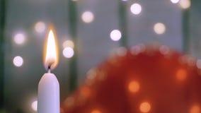 Närbildskott av den vita stearinljuset med brand på bakgrund med ljus i bokeh red steg