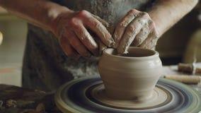 Närbildskott av denfärdiga keramiska krukasnurret på att kasta hjulet och händer som klipper lera med yrkesmässiga hjälpmedel arkivfilmer