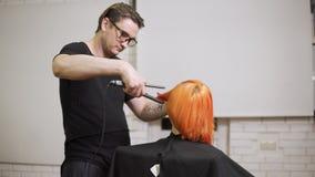 Närbildskott av en kvinna som har hennes hår att rätas ut av en manlig yrkesmässig hårstylist i hårsalong Skjutit i 4k lager videofilmer