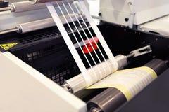 Närbildskott av etiketter som tillverkar på flexoprintingmaskinen Fotodetalj av matrisavfalls eller klippningborttagning från bin arkivfoton