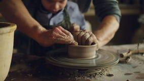 Närbildskott av fyra händer farfar och sonson som gjuter den keramiska krukan på snurret som tillsammans kastar hjulet krukmakeri arkivfilmer