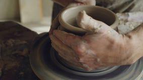 Närbildskott av manliga händer som arbetar med lera på snurrkeramiker` s som kastar hjulet och att dekorera krukan som gör prydna arkivfilmer