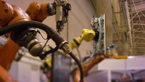 Närbildskott av två automatiska robotic armar i process på fabriksbakgrund stock video