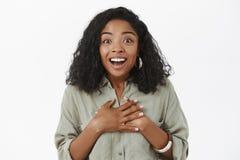Närbildskottet av den förtjusta roade och lyckliga unga charmiga afrikansk amerikankvinnan med det lockiga frisyrinnehavet gömma  royaltyfria foton