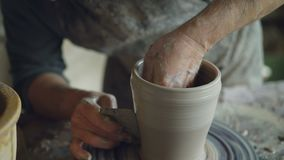 Närbildskottet av händer för keramiker` som s slätar den göt krukan med det yrkesmässiga hjälpmedlet på att kasta för snurr, rull lager videofilmer