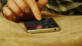 Närbildskottet av kvinnlign räcker den rörande smartphonen, medan ligga på sängarket arkivfilmer