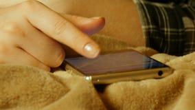 Närbildskottet av kvinnlign räcker den rörande smartphonen, medan ligga på sängarket lager videofilmer