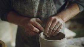 Närbildskottet av manliga händer som slätar den göt lerakrukan med den våta svampen på snurrkeramiker` s, rullar in den hem- stud arkivfilmer