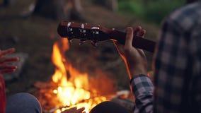 Närbildskottet av mannen räcker att spela gitarren och den kvinnliga handinflyttningdansen med brinnande lägereld i bakgrund stock video