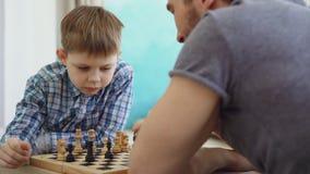 Närbildskottet av två personer avlar och sonen som spelar schack och att tänka om den nästa flyttningen och rörande schackpjäser  arkivfilmer