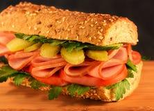 Närbildsmörgås med skinka, den inlagda gurkan, tomaten och gräsplaner svart bulle isolerad sesam arkivfoto
