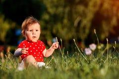 Närbildsommarståenden av härligt behandla som ett barn flickan på gräsmattan i parkera Arkivfoto