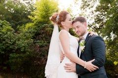 Närbildstående av älskvärda älska kyssande nygifta personer för ett par på en bakgrund av sommargrönska royaltyfri fotografi