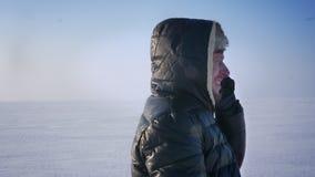 Närbildstående av affärsmannen i huv som upptaget talar på mobiltelefonen i snööken lager videofilmer
