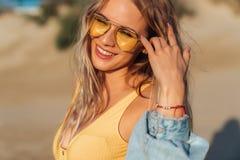 Närbildstående av att charma flickan i solglasögon och den gula baddräkten som poserar i solljuset royaltyfri foto