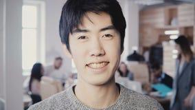 Närbildstående av att le asiatiskt le för affärsman Lycklig ung man som ser kameran, lag som arbetar i bakgrund 4K lager videofilmer