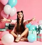 Närbildstående av den attraktiva flickan med gåva och ballonger för studio royaltyfria foton