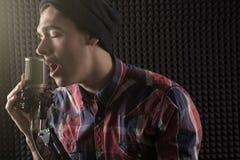 Närbildstående av den emotionella unga grabben som sjunger med hans ögon som stängs i ett lock som framme står av mikrofonställni Arkivfoto