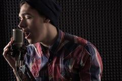 Närbildstående av den emotionella unga grabben som sjunger med hans ögon som stängs i ett lock som framme står av mikrofonställni Royaltyfri Foto