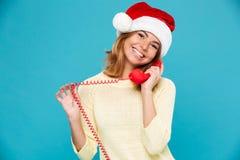 Närbildstående av den gulliga brunettkvinnan i hatt för jultomten` som s talar på den retro telefonen som ser kameran Arkivfoton