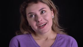 Närbildstående av den gulliga kvinnan som lyckligt ler och gråter i lycka på svart bakgrund lager videofilmer