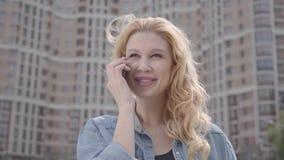Närbildstående av den gulliga le säkra blonda kvinnan som framme talar vid mobiltelefonen av skyskrapan stads- livsstil lager videofilmer
