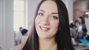 Närbildstående av den härliga europeiska kvinnliga affärskvinnan med långt rakt hår, blåa ögon i det moderiktiga kontoret 4K lager videofilmer