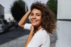 Närbildstående av den härliga le unga kvinnan med långt brunetthårflyg på vinden arkivfoto