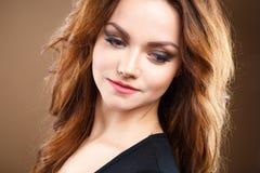 Närbildstående av den härliga sexiga unga kvinnan med långt brunt hår över brun bakgrund Royaltyfri Fotografi