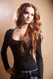 Närbildstående av den härliga sexiga unga kvinnan med långt brunt hår över brun bakgrund Arkivfoto