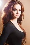 Närbildstående av den härliga sexiga unga kvinnan med långt brunt hår över brun bakgrund Fotografering för Bildbyråer