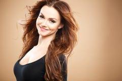 Närbildstående av den härliga sexiga unga kvinnan med långt brunt hår över brun bakgrund Royaltyfria Foton