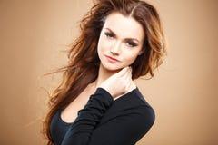 Närbildstående av den härliga sexiga unga kvinnan med långt brunt hår över brun bakgrund Arkivbild