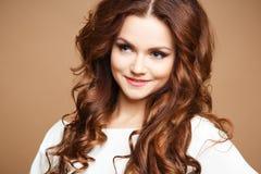 Närbildstående av den härliga sexiga unga kvinnan med långt brunt hår över brun bakgrund Royaltyfria Bilder