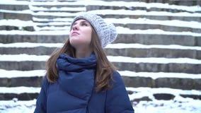 Närbildstående av den härliga unga le caucasian kvinnan i vinteromslag, hatt och halsduk Snöig trä för brunettflicka lager videofilmer