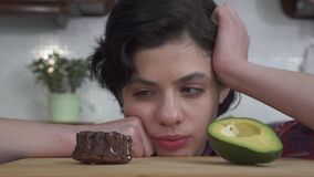 Närbildstående av den hungriga härliga flickan som väljer mellan den lilla smakliga nissemuffin med läcker glasyr på kaka och lager videofilmer