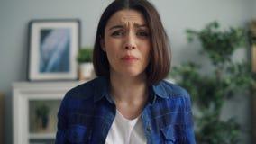 Närbildstående av den ilskna damen som hemma skriker och gör en gest därefter att lämna lager videofilmer