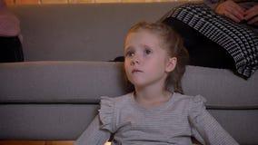 Närbildstående av den lilla caucasian flickan med flätade trådar som uppmärksamt håller ögonen på film i mysig hem- atmosfär lager videofilmer
