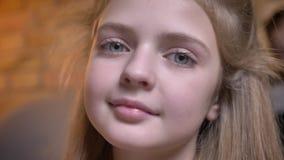 Närbildstående av den lilla nätta caucasian flickan som i stillhet håller ögonen på in i kamera i mysig hem- atmosfär stock video