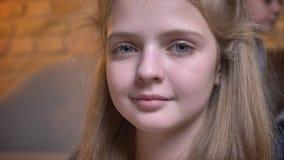 Närbildstående av den lilla nätta caucasian flickan som i stillhet ler in i kamera i mysig hem- atmosfär lager videofilmer