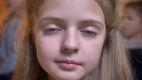 Närbildstående av den lilla nätta caucasian flickan som modestly ler in i kamera i mysig hem- atmosfär stock video