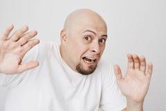 Närbildstående av den livrädda skalliga mannen som lyfter händer som, om se något som är läskig och försöka till försvar som stir Arkivfoto
