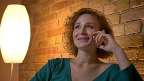 Närbildstående av den ljust rödbrun lockig-haired caucasian flickan som gärna talar på smartphonen på mysig hem- bakgrund stock video
