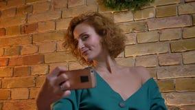 Närbildstående av den ljust rödbrun lockig-haired caucasian flickan som gör selfie-foto genom att använda smartphonen på mysig he stock video